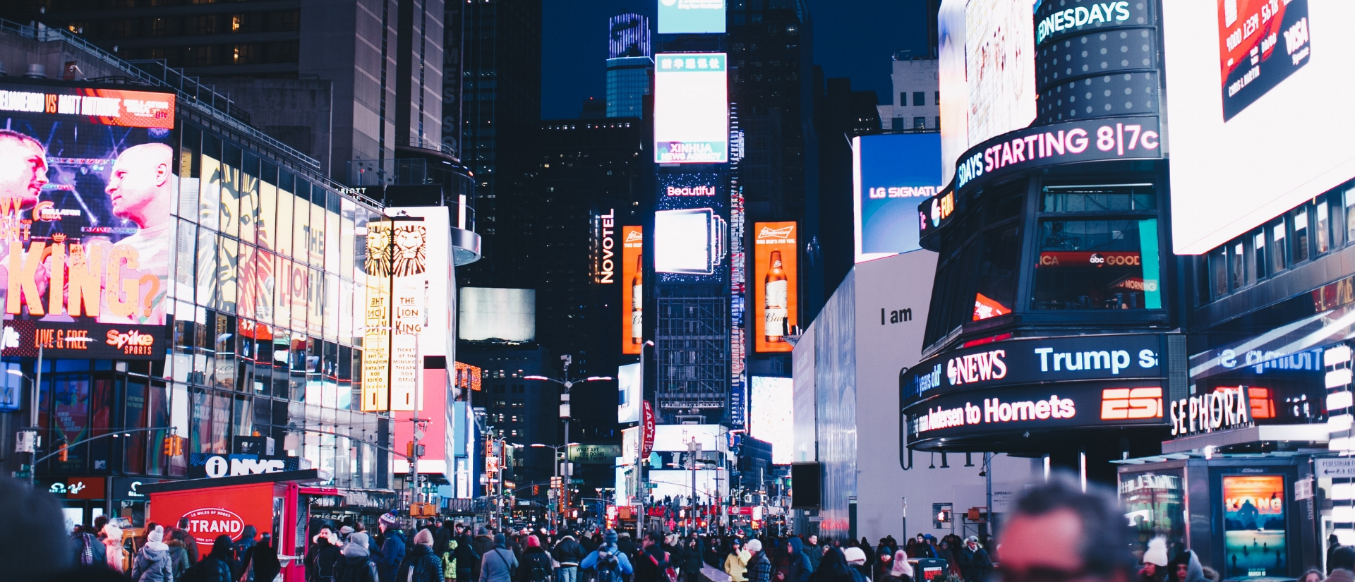 digital signage displays showing content in busy new york street